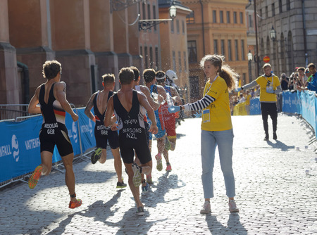 elite: STOCKHOLM - AUG 26, 2017: Official giving water bottle to running triathletes in old town in the Mens ITU World Triathlon series event August 26, 2017 in Stockholm, Sweden