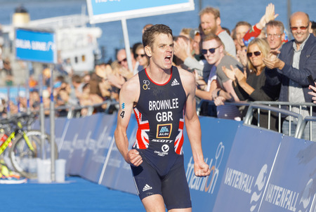 he: STOCKHOLM - AUG 26, 2017: Running triathletes Jonathan Brownlee realize he is going to win the race in the Mens ITU World Triathlon series event August 26, 2017 in Stockholm, Sweden Editorial