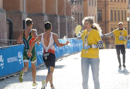 elite: STOCKHOLM - AUG 26, 2017: Official giving water bottle to running triathlete Bergere (FRA) in the Mens ITU World Triathlon series event August 26, 2017 in Stockholm, Sweden Editorial