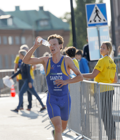 elite: STOCKHOLM - AUG 26, 2017: Running triathlete Gabriel Sandor (SWE) splashing water from a bottle in his face in the Mens ITU World Triathlon series event August 26, 2017 in Stockholm, Sweden