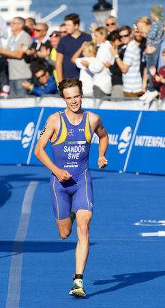 elite: STOCKHOLM - AUG 26, 2017: Running triathlete Gabriel Sandor (SWE) close to the finish line, audience in the background in the Mens ITU World Triathlon series event August 26, 2017 in Stockholm, Sweden