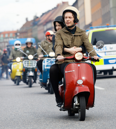 STOCKHOLM, SWEDEN - SEPT 02, 2017: Male and female mods wearing old fashioned clothes driving old fashioned vespa scooter at the Mods vs Rockers event at the Saint Eriks bridge, Stockholm, Sweden, September 02, 2017