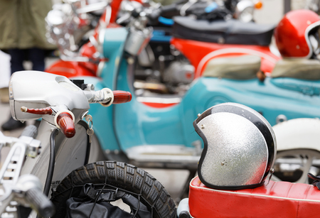 STOCKHOLM, SWEDEN - SEPT 02, 2017: Retro MC helmets on old fashioned colorful vespa scooter and other scooters in the background at the Mods vs Rockers event at the Saint Eriks bridge, Stockholm, Sweden, September 02, 2017