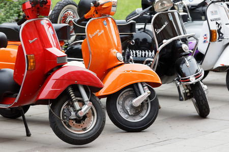 STOCKHOLM, SWEDEN - SEPT 02, 2017: Parked colorful red, orange and black old fashioned vespa scooters  at the Mods vs Rockers event at the Saint Eriks bridge, Stockholm, Sweden, September 02, 2017