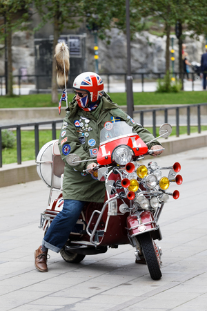 STOCKHOLM, SWEDEN - SEPT 02, 2017: Mods wearing uk flag helmet and driving retro vespa scooter with lots of lamps and horns at the Mods vs Rockers event at the Saint Eriks bridge, Stockholm, Sweden, September 02, 2017