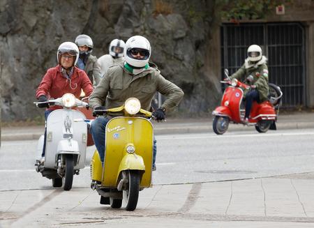 STOCKHOLM, SWEDEN - SEPT 02, 2017: Group of mods in parka jackets driving vintage vespa scooter at the Saint Eriks bridge, Stockholm, Sweden, September 02, 2017