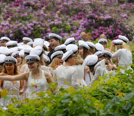 ESTOCOLMO, SUECIA - 13 DE JUNIO DE 2017: Estudiantes de graduación sonrientes, arbusto hermoso del llilac en el fondo en la escuela de baile Balettakademien, el 13 de junio de 2017, Estocolmo, Suecia
