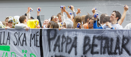 STOCKHOLM, SWEDEN - JUN 13, 2017: Group of happy teenagers squirting beer after graduation on a truck bed at the dance school Balettakademien, June 13, 2017, Stockholm, Sweden Editorial