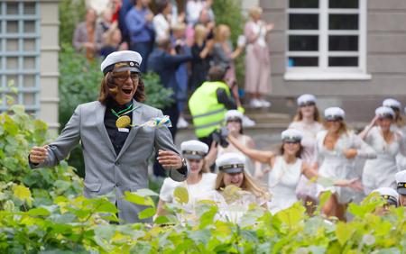 STOCKHOLM, SWEDEN - JUN 13, 2017: Happy teenagers wearing graduation caps running out from school after graduation at the dance school Balettakademien,June 13 2017,Stockholm,Sweden