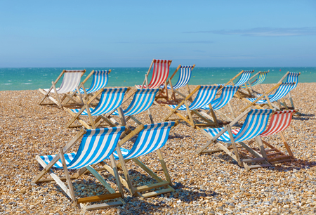 Many Classic Red And Blue Deckchairs On The Beach, Green Sea In The  Background Stock