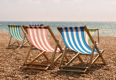 Classic Red, Blue, Green And White Striped Deckchairs On The Beach, The Sea