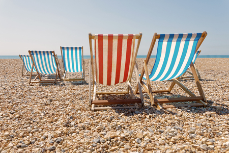 Peaceful Day On The Pepple Beach, Classic Red And Blue Deckchairs, Blue Sea  In