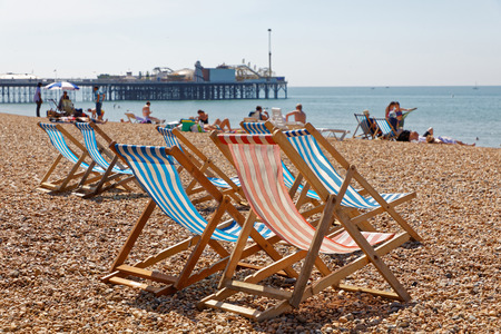 BRIGHTON, GREAT BRITAIN   JUN 17, 2017: Classic Deckchairs And People  Sunbathing On