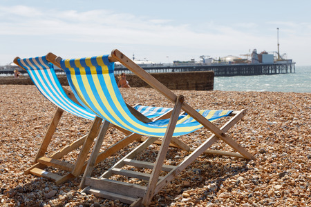 brighton: BRIGHTON, GREAT BRITAIN - JUN 17, 2017: Closeup of classic deckchairs and people sunbathing on the pebble beach at the Brighton pier a sunny day. June 17, 2017 in Brighton, Great Britain Editorial