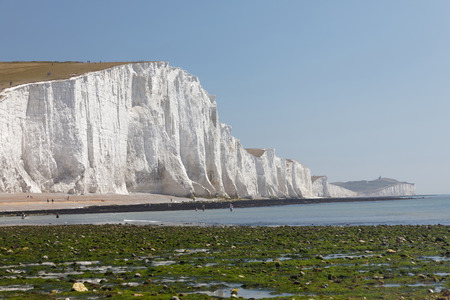 SUSSEX, GREAT BRITAIN - JUN 18, 2017: Distant people sunbathing having the white chalk cliffs in the Seven Sisters Country Park in the background. June 18, 2017 in Sussex, Great Britain