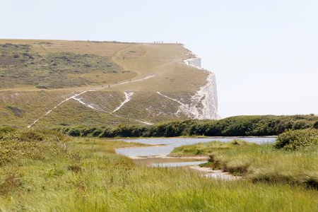 The beautiful white chalk cliffs in the Seven Sisters Country Park in the summer. Distant people walking close to the precipice