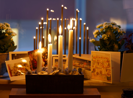 Typical swedish advent candle stick holder with decorations and all four candles burning the 4th sunday in december. Christmas cards in the window