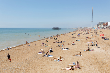 BRIGHTON, GREAT BRITAIN - JUN 17, 2017: Sunbathing people on the Brighton beach, West pier in the background. June 17, 2017 in Brighton, Great Britain