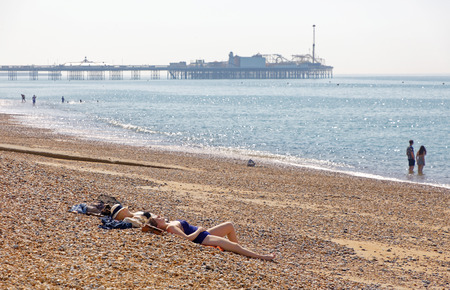 BRIGHTON, GREAT BRITAIN - JUN 17, 2017: Sunbathing people on the Brighton beach, Brighton pier in the background. June 17, 2017 in Brighton, Great Britain Editorial