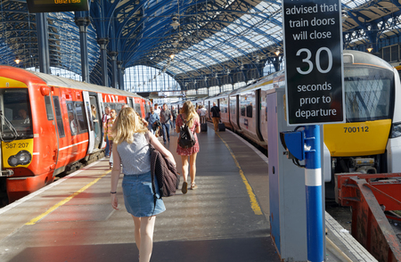 BRIGHTON, GREAT BRITAIN - JUN 19, 2017: People walking on the platform to catch a train in the train station in Brighton, UK. June 27, 2017 in Brighton, Great Britain Editoriali