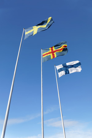 Flags from Sweden, Aland and Finland on flag poles, blue sky and white cloudes Stock Photo