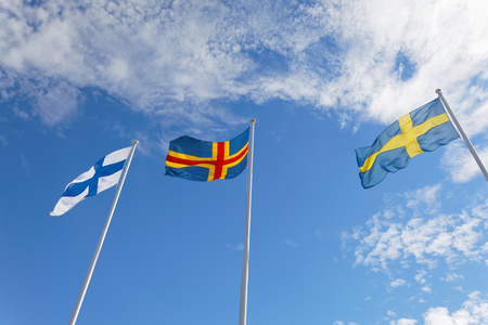Flags from Finland, Aland and Sweden on flag poles, blue sky and white cloudes