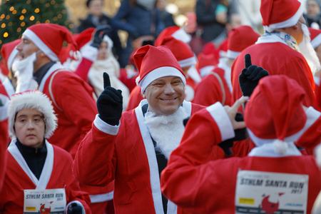 STOCKHOLM, SWEDEN - DEC 10, 2017: Smailing Santa in traditional red dress and beard in the Stockholm Santa Run in Sweden, December 10, 2017