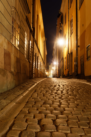 Narrow alley in the Old Town during night in central Stockholm. Warm yellow colors Imagens