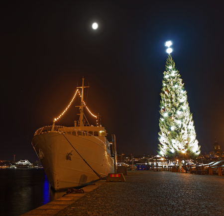 Gigantic christmas tree decorated with red and white  and a boat in central Stockholm, Sweden