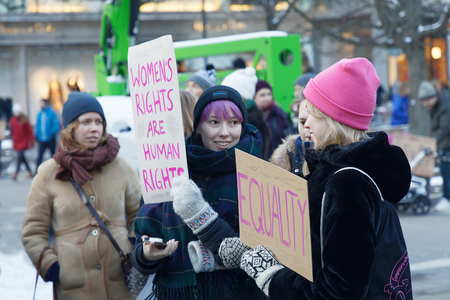 STOCKHOLM, SWEDEN - JAN 21, 2018: Young women holding a placard in the Womens March, a worldwide protest for women's rights in central Stockholm, Norrmalmstorg, Sweden, January 21, 2018