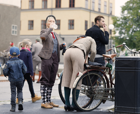 STOCKHOLM - SEPT 23, 2017: Women dressed in traditional tweed clothes fixing their vintage bicycles in the Bike in Tweed event September 23, 2017 in Stockholm, Sweden