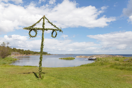 Tiny maypole in the Swedish archipelago, blue sky and white clouds in the background Stock Photo