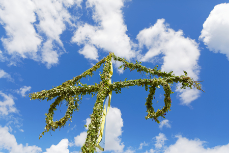 Maypole made of green leaf and the blue sky and some white clouds behind Stock Photo
