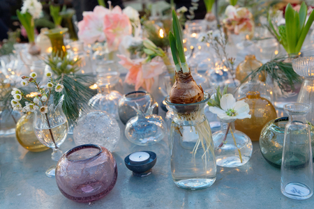 Many Glass Vase In Different Shapes With Flowers On A Table Stock