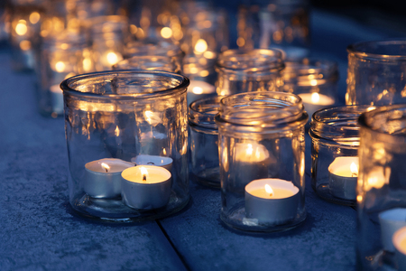 Many lantern made of glass and tealight glowing in the night Stock Photo