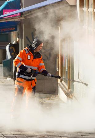 STOCKHOLM, SWEDEN - NOV 07, 2017: Official in orange uniform working to remove graffiti using steem on a wall in central Stockholm, Sweden, November 07, 2017 Editorial