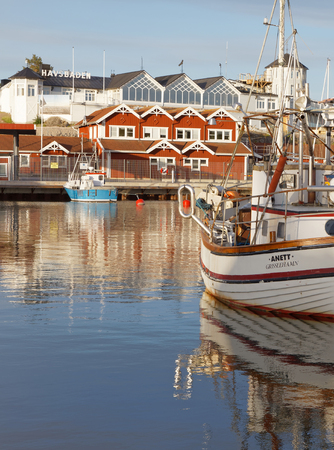 GRISSLEHAMN, SWEDEN - JUL 08, 2017: Morning light and traditional fishing boats in the small harbor early morning, a hotel in th background. Grisslehamn Sweden, July 08, 2017 Editorial