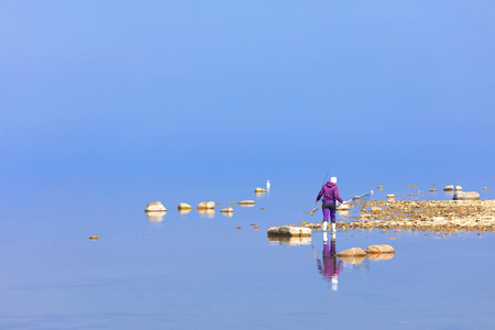 Female angler reflecting in the blue calm sea trying to catch trout at Aleklinta on the island Oland, Sweden Standard-Bild