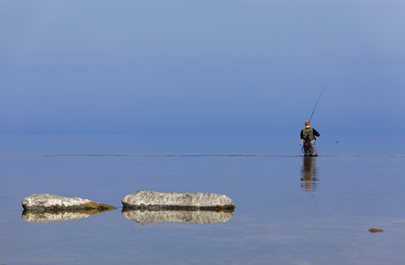Angler walking in the blue calm sea trying to catch trout at Aleklinta on the island Oland, Sweden Standard-Bild