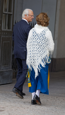 STOCKHOLM, SWEDEN - JUN 06, 2018: Rear view of the swedish queen and king Silvia and Carl Gustaf Bernadotte XVI outside the castle to celebrate the swedish national day June 06 in Stockholm
