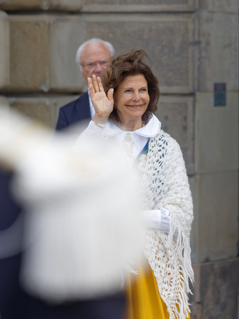 STOCKHOLM, SWEDEN - JUN 06, 2018: The swedish queen Silvia Bernadotte waving to the people outside the castle, the king Carl Gustaf Bernadotte XVI in the background, June 06 in Stockholm 写真素材