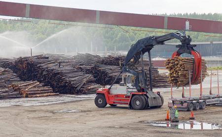 Gran máquina que carga madera en la fábrica de pulpa y papel. Foto de archivo