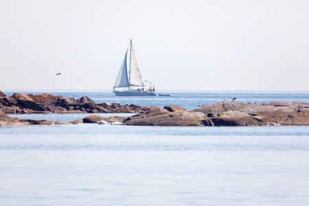 Sailship on the blue ocean in the swedish archipelago, islets in the foreground