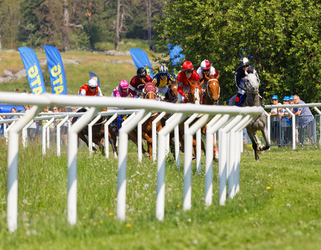 STOCKHOLM, SWEDEN - JUNE 06, 2019: Tough fight between many jockeys riding arabian race horses in a curve at ATG Nationaldags Galoppen at Gardet. June 6, 2019 in Stockholm, Sweden