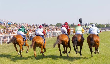 Estocolmo, Suecia - 06 de junio de 2019: Vista trasera de coloridos jinetes en caballos de carrera, audiencia en el fondo en Nationaldags Galoppen en Gardet. 6 de junio de 2019 en Estocolmo, Suecia
