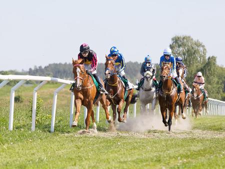 STOCKHOLM, SWEDEN - JUNE 06, 2019: Side front view of colorful jockeys riding arabian race horses at ATG Nationaldags Galoppen at Gardet. June 6, 2019 in Stockholm, Sweden 報道画像
