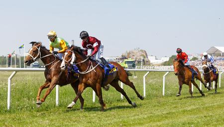 STOCKHOLM, SWEDEN - JUNE 06, 2019: Jockeys riding arabian race horses side by side on the race track at ATG Nationaldags Galoppen at Gardet. June 6, 2019 in Stockholm, Sweden