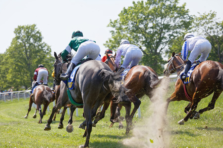 STOCKHOLM, SWEDEN - JUNE 06, 2019: Rear view of standing colorful jockeys on race horses riding in a curve at Nationaldags Galoppen at Gardet. June 6, 2017 in Stockholm, Sweden 報道画像