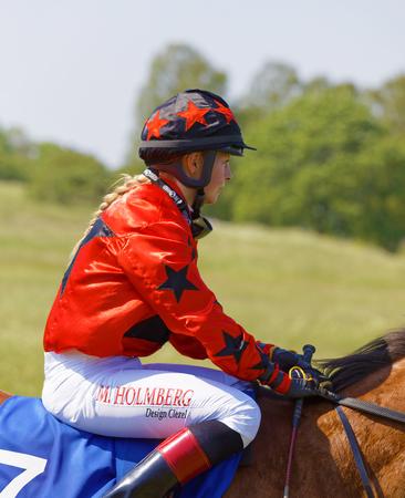 STOCKHOLM, SWEDEN - JUNE 06, 2019: Closeup of jockey Malin Holmberg riding a gallop horse at ATG Nationaldags Galoppen at Gardet. June 6, 2019 in Stockholm, Sweden