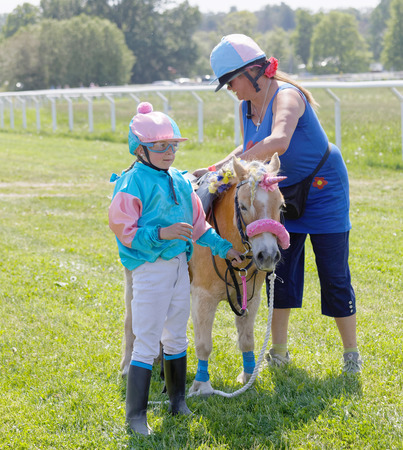 STOCKHOLM, SWEDEN - JUNE 06, 2019: Young jockey holding a cute pony dressed as a unicorn on the race track at Nationaldags Galoppen at Gardet. June 6, 2019 in Stockholm, Sweden 報道画像
